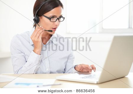 Pretty Latin Employee Talking On Headphones