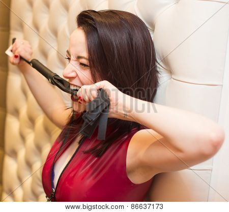 Pretty Young Woman Biting A Leather Whip