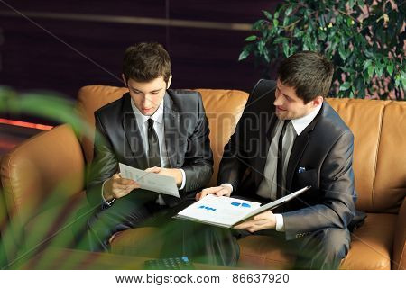 two young businessmen discussing project at meeting