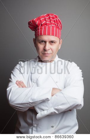 Smiling chef with red hat, studio shot over gray background