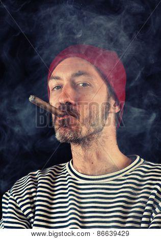 Portrait of sailor man smoking a cigar, shot over black background