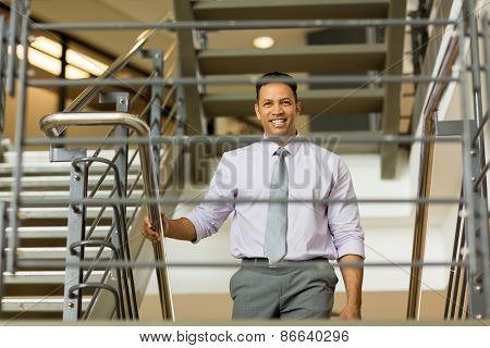 handsome middle aged businessman walking up stairs