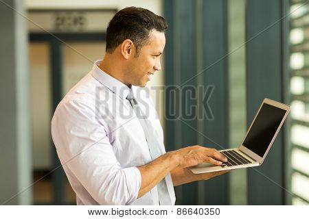 modern middle aged business man looking at computer screen