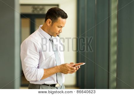 handsome middle aged businessman texting on his smart phone
