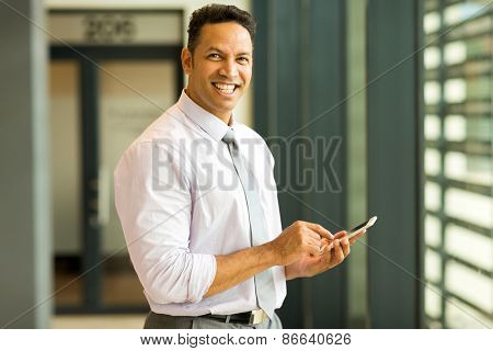happy middle aged business executive using smart phone in office