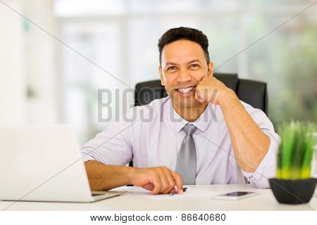 handsome businessman sitting in office looking at the camera