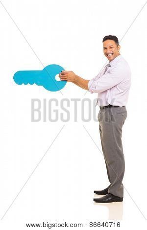 side view of happy middle aged man opening with a huge key isolated on white