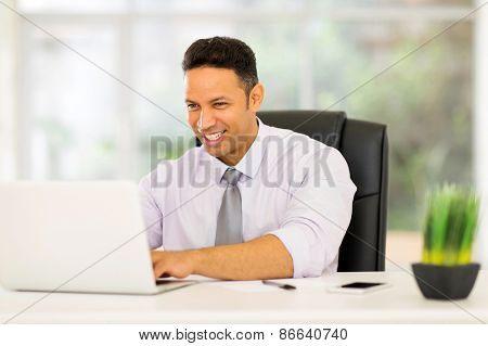 professional mid age corporate worker working on laptop