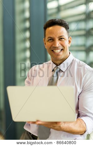 good looking corporate worker holding laptop