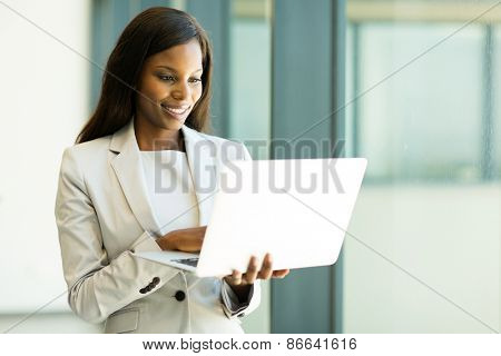 beautiful african businesswoman reading email on her laptop