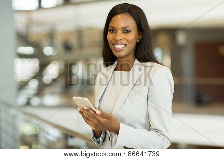 cheerful black businesswoman with smart phone in modern office