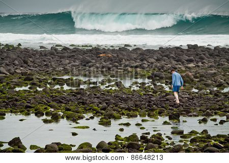 Unidentified tourist walking along the rocky coastline in a scenic beach of San Cristobal Island in