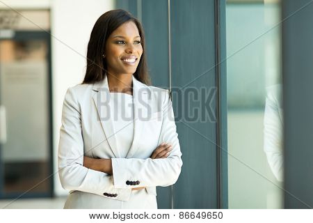 happy young african businesswoman looking out the window