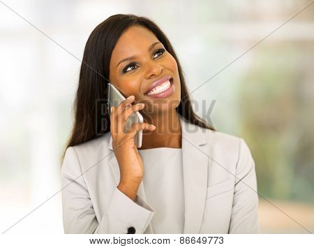 smiling young african business executive talking on smart phone