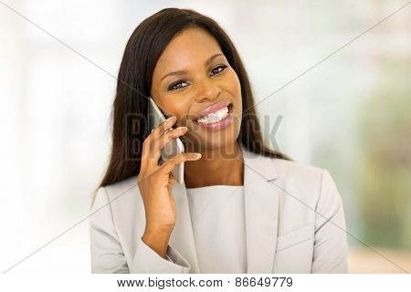 cheerful young afro american woman talking on cell phone