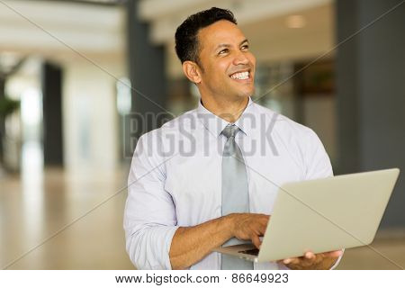 smiling mature business man holding laptop computer in office