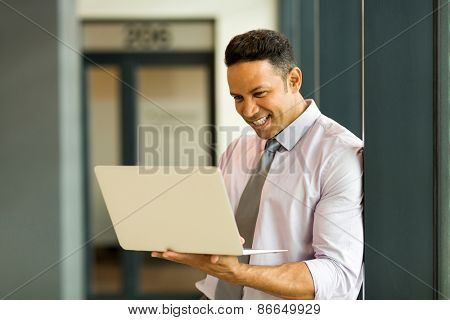 mid age office worker working on laptop in modern office