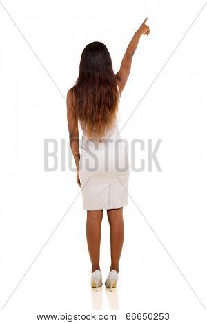 rear view of young african woman pointing at empty copy space