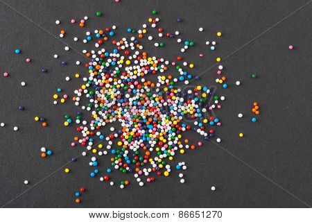 Colorful Round Sprinkles Spilled On Black Background, Isolated