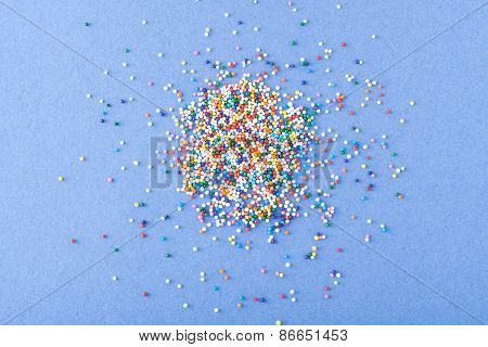 Colorful Round Sprinkles Spilled On Blue Background, Isolated