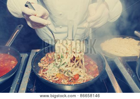 Chef frying mussels with pasta on commercial kitchen, toned image