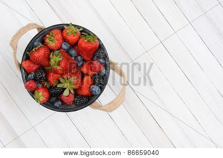 High angle shot of a bucket of fresh picked berries on a rustic whitewashed wood table. The pail is set to the left side leaving copy space.