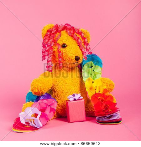 Stuffed birthday bear with present on pink background