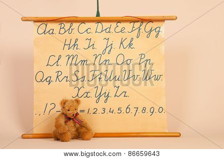 hand made bear sitting in front of vintage lesson with letters and figures