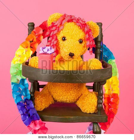 Stuffed birthday bear with present in child chair on pink background
