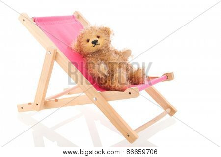 Stuffed hand made bear in beach chair isolated over white background