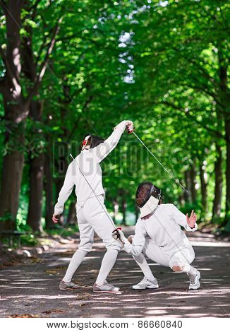 Two rapier fencers women fencing on park path