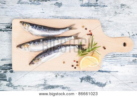 Fresh Anchovy Fish On Wooden Kitchen Board.