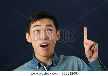 Funny young Asian man pointing his index finger and looking upward