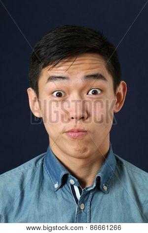 Astonished young Asian man looking at camera