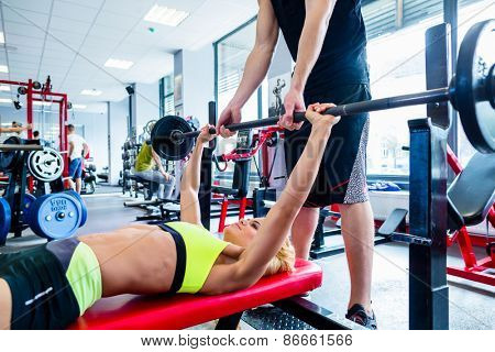 Woman with personal trainer at bench press in gym exercising for better fitness