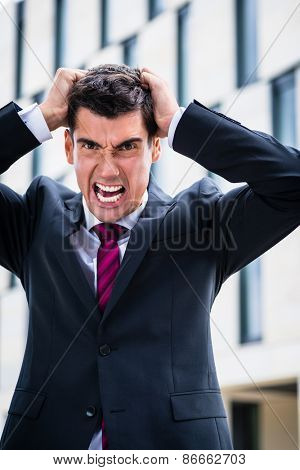 Angry business man tearing his hair in despair