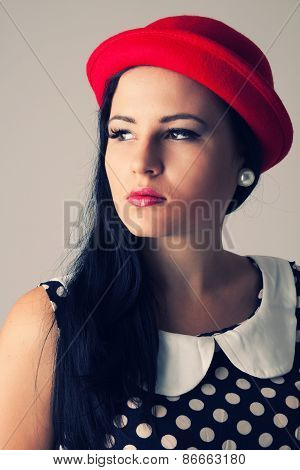 Young Woman With Thoughtful Look In Red Hat