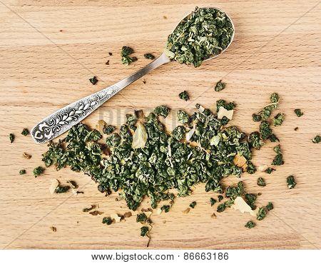 Green Tea In An Iron Spoon On Wooden