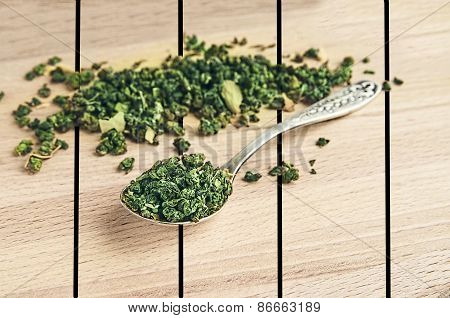 Green Tea In An Iron Spoon On Wooden Table