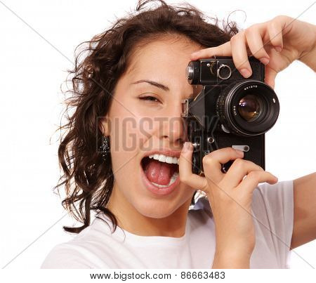 Close up lifestyle portrait of young pretty photographer girl making shot on her vintage camera, white background