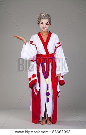 Beautiful young woman in white kimono dress on gray background