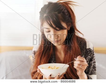 asian teen girl eating chicken noodle soup
