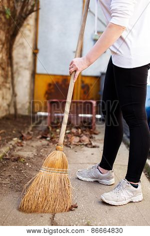 Woman Sweeping On Backyard