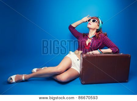 Beautiful Pin-up Girl Posing With Vintage Suitcase Against Blue Background