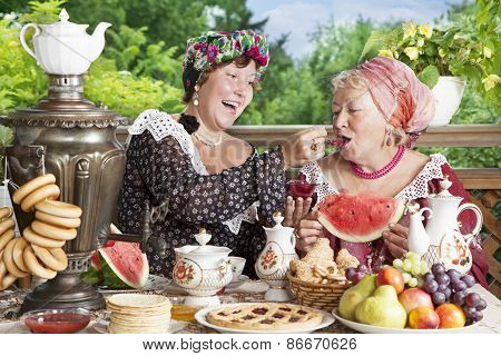 Two Cheerful Women Drinking Tea  With Bagels And Jam Outdoors