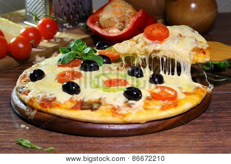 Piece Of A Pizza With The Fused Cheese And A Tomato On A Wooden Shovel