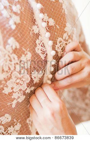 Bride putting on her white wedding dress