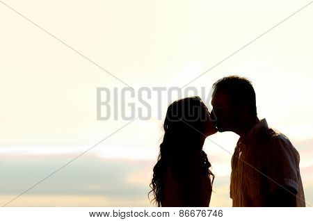 Couple Kissing At Sunset Backlit
