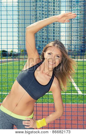 Athletic Smiling Young Woman Doing Morning Exercises On Sports Ground