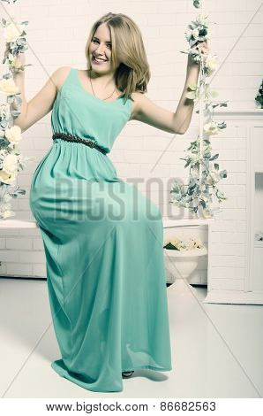 The Beautiful Blonde With Blue Eyes In The Green Dress On A Swin